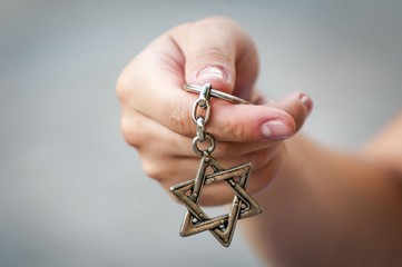 "Young woman's hand holding a David Star (""Magen David"") key chain. The State of Israel, Judaism, Zionism concept image."