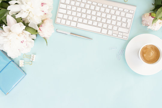 Flat lay home office workspace background with white modern keyboard, notebook and peony flowers, copy space on blue background
