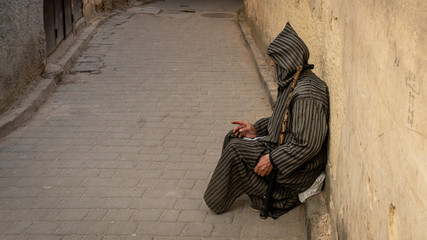 Anonymous poor beggar in the street of Fez, Morocco.
