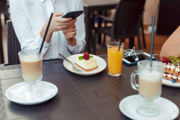 women's hands making photo of sweet dessert on mobile phone while sitting in comfortable restaurant