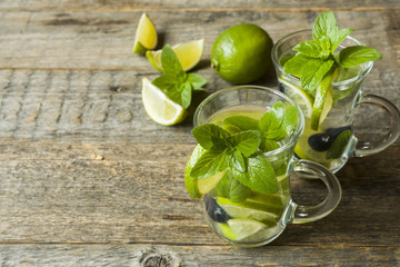 Fresh citrus lemonade in a glass of lime on a wooden background. Copy space for text.