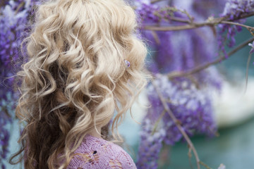 Fotomurales - Girl is in blooming wisteria. Beautiful flowers garden in spring. Woman is wearing in lilac knitted shawl and has blonde curly hair.