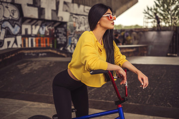 Sexy slim fit brunette woman in sport casual outfit in a skate park. Active leisure on a bicycle