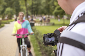 Man make video of a young woman in sports wear relaxing in park after riding a bicycle. Fit, slim brunette woman with cheerful smile. Summer weather, outdoors leisure.