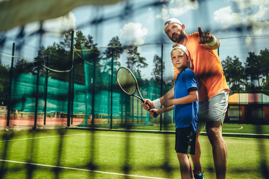 Portrait of concentrated male trainer teaching serene boy playing tennis outdoor. He pointing hand