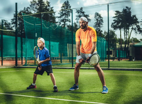 Full length portrait of concentrated bearded male couch playing with focused kid on contemporary court. They keeping rackets in hands