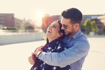 Successful american businessman covering woman with USA flag