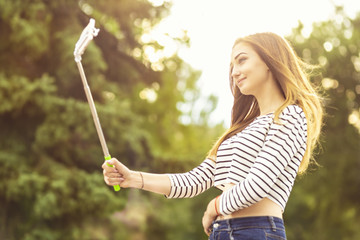 portrait of a beautiful smiling girl making a photo for a social network in a city park on a smartphone using a selfie stick