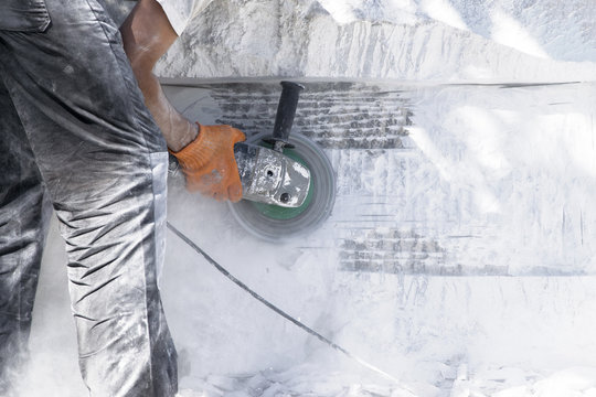 .The worker works as a grinder on a white stone.
