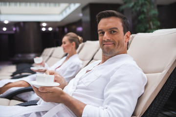Focus on waist up portrait of joyful male sitting on deckchair with cup of favorite hot drink. He is enjoying relaxation time. Young woman in bathrobe is on background