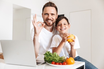 Photo of happy smiling man 30s and boy 8-10 reading recipe on laptop, for cooking meal with vegetables in kitchen