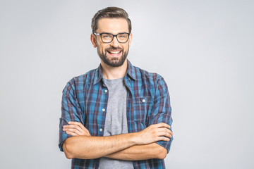 Happy young man. Portrait of handsome young man in casual shirt keeping arms crossed and smiling while standing against grey background Wall mural