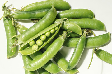 pods of green peas with closed and opened flaps and peas
