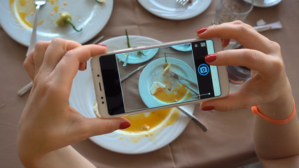 The process of photographing a smartphone. The girl is making a photo for the social network. Plates with the remains of food.