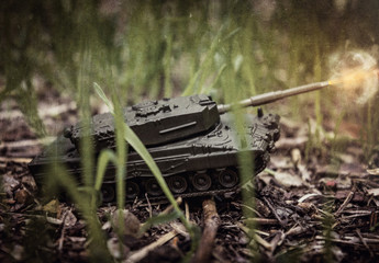 Toy tank on nature background with ground and green grass