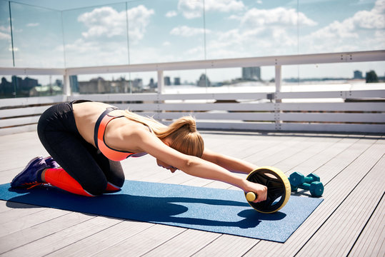 Slim woman is using abs roller for exercising. She is having workout with equipment including dumbbells on roof of sunny house. She is kneeling and bending body while handling outfit