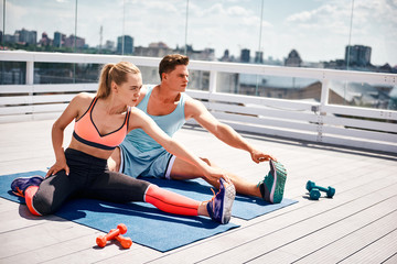 Concentrated man and woman are training flexibility on mats. They are sitting on bent leg while straightening other. Couple is having workout together on urban terrace