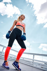 Low angle of slender woman having combat workout. She is standing in sportswear and gloves and looking forward with confidence. Girl is training on wide open balcony under sky