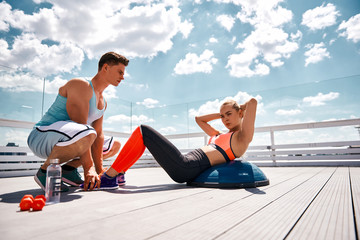 Low angle of strained lady doing crunches on half-ball. Strong male friend is holding her feet for helping with exercise. They are training together with dumbbells and other outfit on sunny balcony