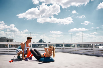 Female is doing crunches on BOSU ball while her male friend is holding her feet. They are having joint workout with sport equipment on top of urban high building. Copy space in right side