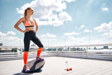 Concentrated fir lady is exercising with dumbbell and resistance band on sunny terrace of skyscraper. She is balancing on BOSU platform and looking forward. Copy space in right side