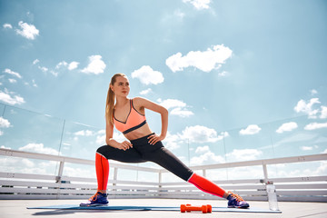 Low angle of slim woman exercising on open terrace under lovely sky. She is doing side lunges and preparing for training with dumbbells. Doing fitness in open air concept