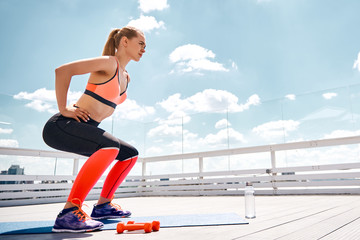 Athletic lady is having workout with own weight and dumbbells on balcony under blue sky. She is doing sit-ups while putting hands on waist. Copy space in right side