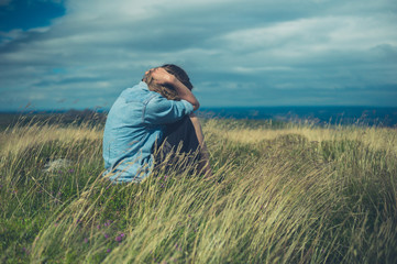 Sad woman in field on windy day