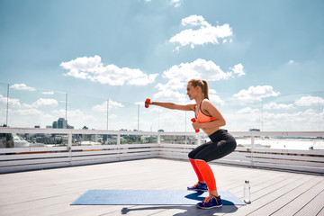 Positive fit lady is having leg and shoulder work out on roof of city house. She is doing sit-ups and pushing arm forward while lifting dumbbell. Copy space in left side