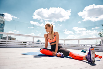 Slender woman is having break in training with dumbbells on terrace of high urban building. She is sitting on one bent leg and straighten another. Exercising in sunny weather concept