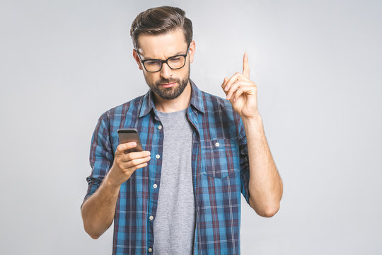 Idea! Young stylish hipster guy dressed in shirt, holds smart phone, reads something attentively, raises index finger, quotes someone words, proves his rightness. People and technology concept.