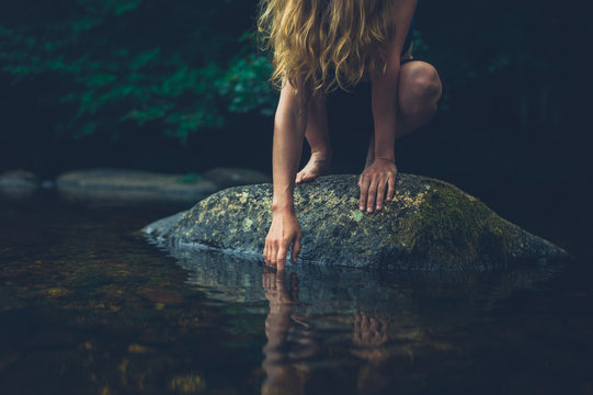 Young woman sitting on rock in a river