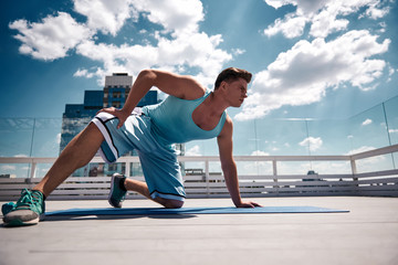 Ripped young man is having workout outdoors during warm sunny day. He is standing on one knee and hand while looking ahead. He is training body on terrace of urban building