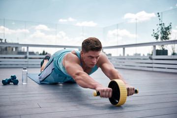 Concentrated young guy is exercising with sport equipment on roof of urban building. He is kneeling on mat and rolling forward outfit wheel for working on abdominal muscles. He is going to continue