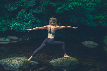 Yoga woman in warrior pose on rock in river