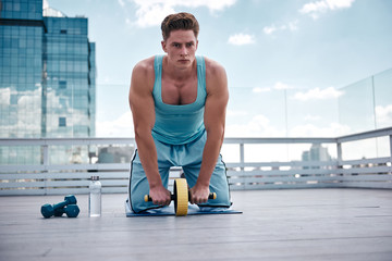 Young ripped guy is kneeling on mat and exercising with abs roller. He is feeling certain and motivated about working out with this equipment and dumbbells later. Athlete is spending active day on