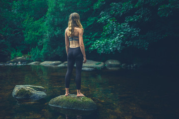 Young fitness woman standing on rock in river