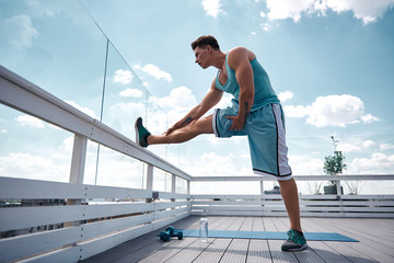 Fit young man is stretching leg while standing and putting it on roof railing. He is getting ready for training outdoors with dumbbells. Male is working out in fresh air concept