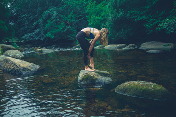Young woman standing on rock in the river