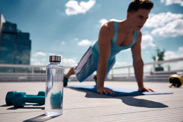 Focus on pair of dumbbells and bottle of water on roof of house in busy city. Young athlete is staying in plank position on background. Training in urban atmosphere concept