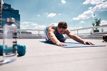 Sportsman is stretching body while exercising with dumbbells on roof in city center. He is sitting on feet and bending body while straightening arms forward. Male is using mat and bottle of water for