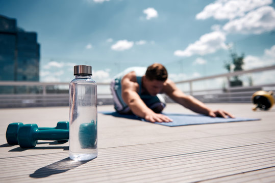 Focus on bottle with soft drink and two dumbbells on terrace of high building in city. Male is stretching on mat on background. Sportsman is spending active sunny day