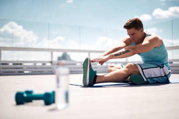 Athlete is stretching on mat while spending time actively on terrace of high building among city. He is sitting on one hip and bending to other straight leg. He is finishing training with dumbbells on