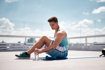 Exhausted athlete is sitting on mat and holding bottle with water. He is going to quench thirst and have short break in training. Male is exercising with dumbbells on roof of skyscraper o sunny warm