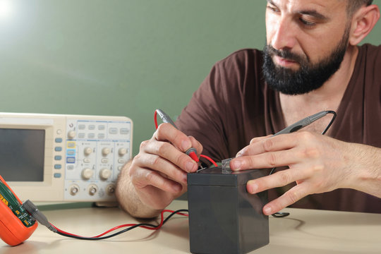 Electrician checks the battery in the laboratory