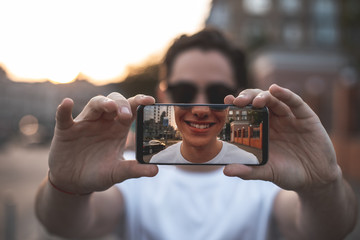 Focus on male hands holding mobile outdoors and making selfie. Young guy is happy and delighted