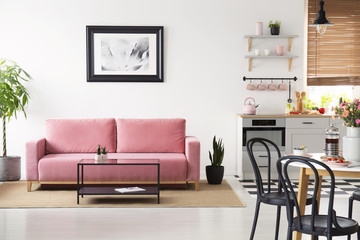 Poster above pink couch in white apartment interior with black chairs at table and kitchenette. Real photo