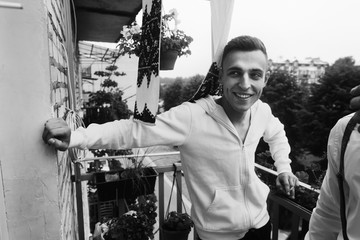 Handsome emotional man in white sweatshirt standing on the balcony, groom smiling, morning before the wedding