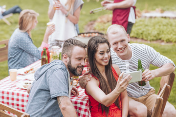 Smiling friends taking selfie during grill party in the garden