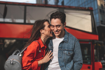 Happy man and woman standing on street with bus on background. They are bonding to each other and smiling